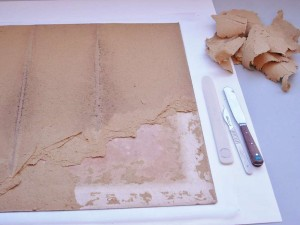 Removing the later strawboard backing using a scalpel, letter opener and spatula